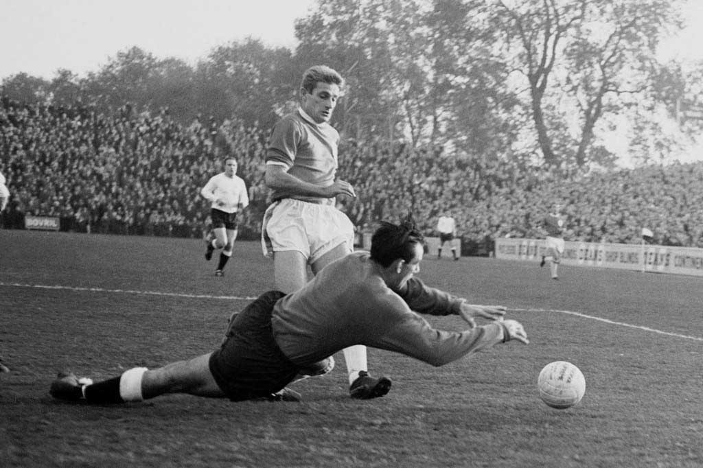 Fulham goalkeeper Tony Macedo dives at the feet of Liverpool's Roger Hunt