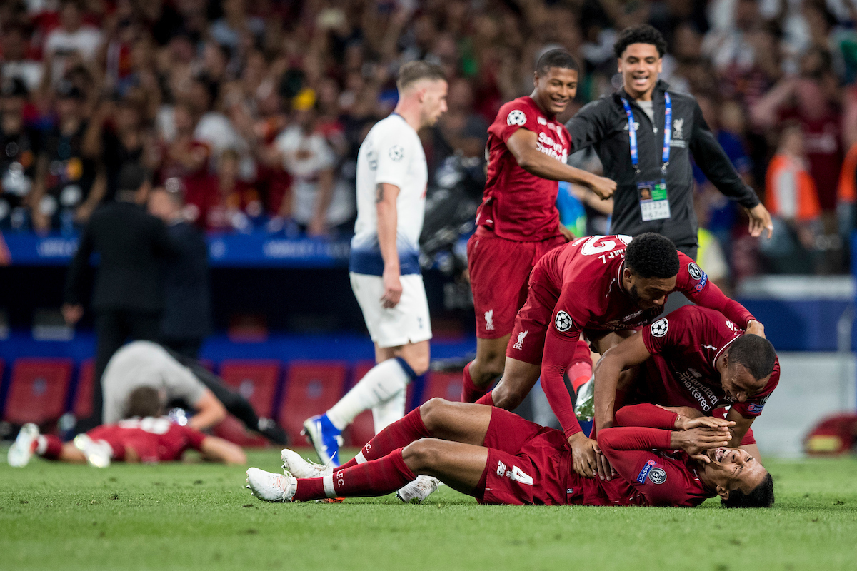 MADRID, SPAIN - SATURDAY, JUNE 1, 2019: Liverpool's Virgil van Dijk collapses to the pitch at the final whistle as team-mates Joel Matip and Joe Gomez embrace him as they celebrate a 2-0 victory in the UEFA Champions League Final match between Tottenham Hotspur FC and Liverpool FC at the Estadio Metropolitano. (Pic by Paul Greenwood/Propaganda)
