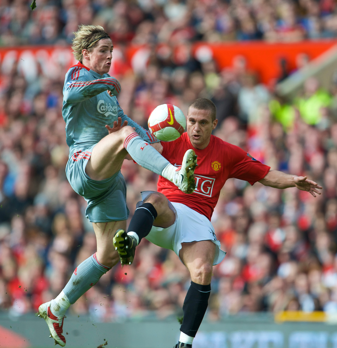 MANCHESTER, ENGLAND - Saturday, March 14, 2009: Liverpool's Fernando Torres powers past Manchester United's hapless Nemanja Vidic on his way to scoring the second goal during the Premiership match at Old Trafford. (Photo by David Rawcliffe/Propaganda)