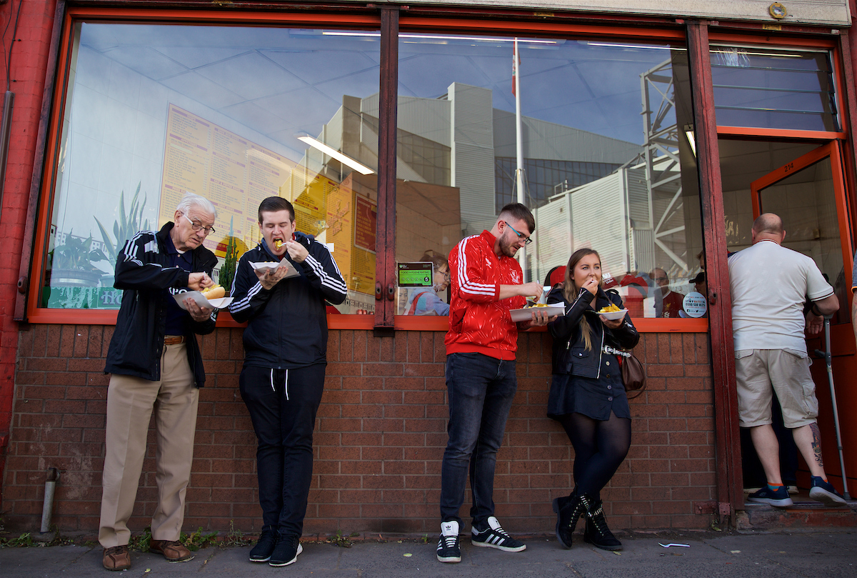 """LIVERPOOL, ENGLAND - Saturday, September 14, 2019: Supporters eat a traditional pre-match meal of chips (fried potatoes) outside the Sing Fong Chinese """"chippy"""" with the stadium reflected in the window before the FA Premier League match between Liverpool FC and Newcastle United FC at Anfield. (Pic by David Rawcliffe/Propaganda)"""
