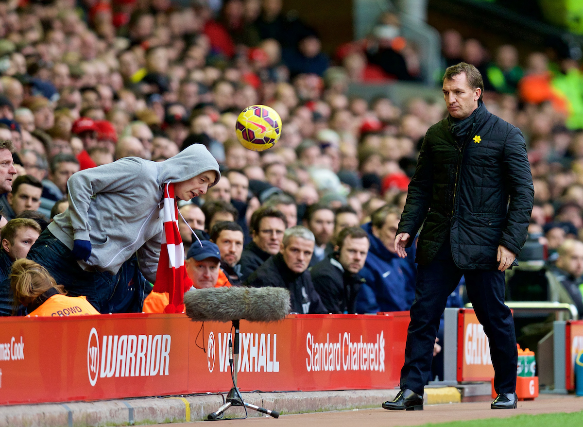 LIVERPOOL, ENGLAND - Sunday, March 1, 2015: Liverpool's manager Brendan Rodgers goes to retrieve the ball but is beaten to it by a supporter during the Premier League match against Manchester City at Anfield. (Pic by David Rawcliffe/Propaganda)