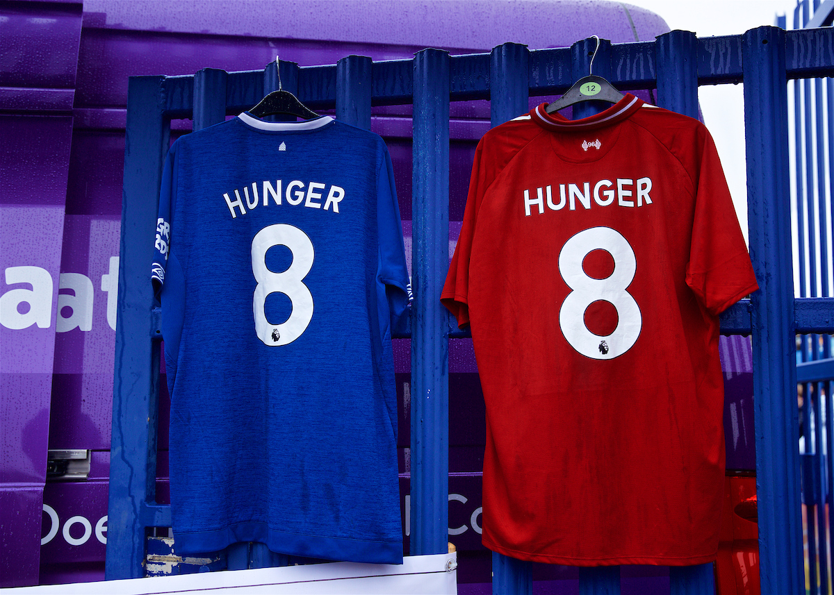 """LIVERPOOL, ENGLAND - Sunday, March 3, 2019: An Everton and Liverpool shirt hanging side--by-side with """"8 Hunger"""" on them at a Food Bank during the FA Premier League match between Everton FC and Liverpool FC, the 233rd Merseyside Derby, at Goodison Park.  Supporters of both clubs give to food banks, set up to help feed people left with no money due to the Conservative government's evil austerity measures. (Pic by Laura Malkin/Propaganda)"""