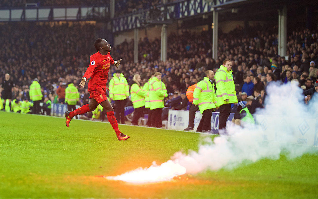 Liverpool's Sadio Mane celebrates scoring the winning goal against Everton in injury time to seal a 1-0 victory, as a red flare lands on the pitch, during the FA Premier League match, the 227th Merseyside Derby, at Goodison Park.