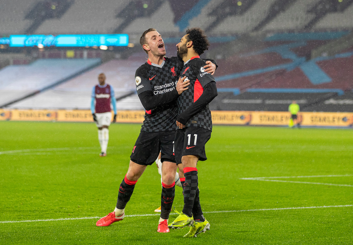 Liverpool's Mohamed Salah celebrates with team-mate captain Jordan Henderson (L) after scoring the second goal during the FA Premier League match between West Ham United FC and Liverpool FC at the London Stadium
