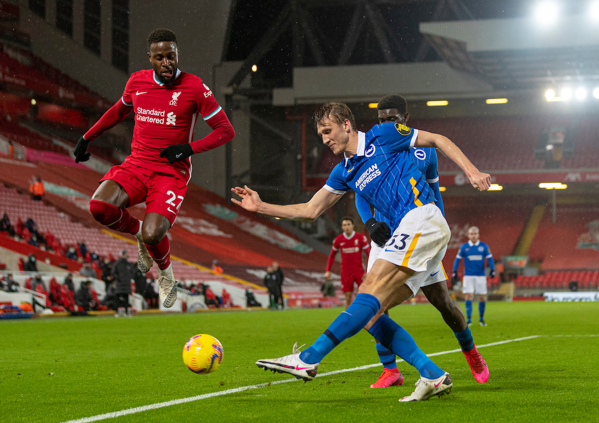 Brighton & Hove Albion's Dan Burn clears the ball under pressure from Liverpool's Divock Origi during the FA Premier League match between Liverpool FC and Brighton & Hove Albion FC at Anfield