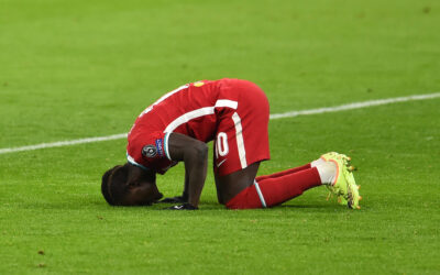 BUDAPEST, HUNGARY - Wednesday, March 10, 2021: Liverpool's Sadio Mané kneels to pray as he celebrates with team-mate Fabio Henrique Tavares 'Fabinho' after scoring the second goal during the UEFA Champions League Round of 16 2nd Leg game between Liverpool FC and RB Leipzig at the Puskás Aréna. Liverpool won 2-0, 4-0 on aggregate.