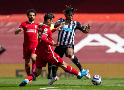 Liverpool's Ozan Kabak tackles Newcastle United's Allan Saint-Maximin (R) during the FA Premier League match between Liverpool FC and Newcastle United FC at Anfield.