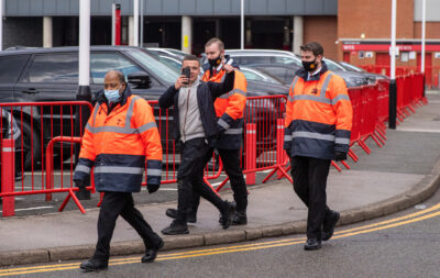 A Manchester United supporter is led away from the stadium by stewards after a fans' protest before the FA Premier League match between Liverpool FC and Manchester United FC at Old Trafford.