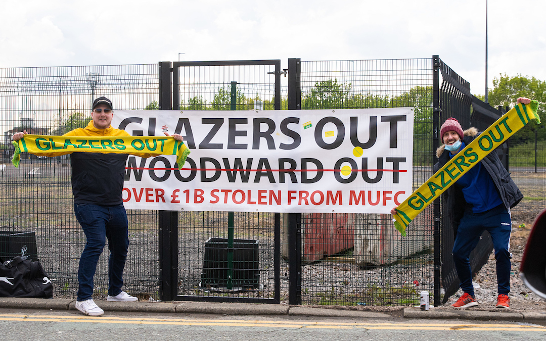 """Two Manchester United supporters protest against the owners with """"Glazers Out"""" scarves and banner outside the ground before the FA Premier League match between Liverpool FC and Manchester United FC at Old Trafford which was postponed due to safety concerns after a number of supporters entered the stadium."""
